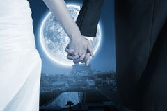 Composite image of close up of cute young newlyweds holding their hands Stock Image