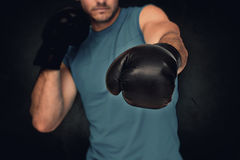 Composite image of close-up of a determined male boxer focused on training. Close-up of a determined male boxer focused on training against dark background stock images