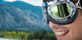 Composite image of close up of happy man wearing aviator goggles Stock Photography