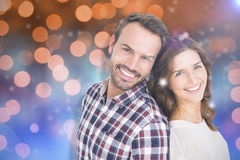 Composite image of close up of happy young couple standing back to back. Close up of happy young couple standing back to back against glowing background Stock Photo