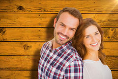 Composite image of close up of happy young couple standing back to back. Close up of happy young couple standing back to back against yellow paint splashed Stock Images