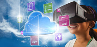 Composite image of close up of little girl holding virtual glasses. Close up of little girl holding virtual glasses against blue sky with clouds Stock Photo