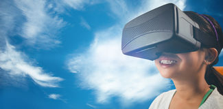 Composite image of close up of little girl holding virtual glasses. Close up of little girl holding virtual glasses against blue sky with clouds Stock Photography