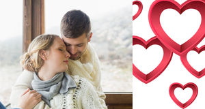 Composite image of close up of a loving young couple in winter clothing. Close up of a loving young couple in winter clothing against pink hearts Stock Photos