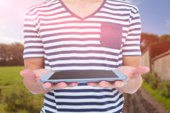 Composite image of close up of man holding tablet against rural landscape Stock Photos