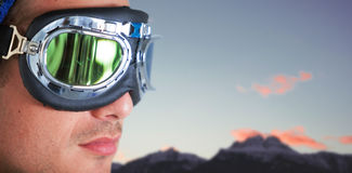 Composite image of close up of man wearing aviator goggles. Close up of man wearing aviator goggles against snowcapped mountains against sky royalty free stock photo