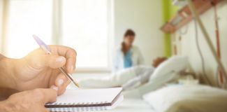 Composite image of close up of man writing in notepad Royalty Free Stock Image