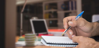 Composite image of close up of man writing in notepad Royalty Free Stock Photography