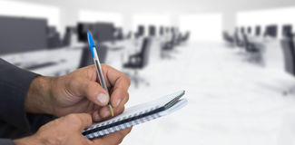 Composite image of close up of man writing in spiral book Stock Photography