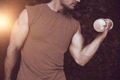 Composite image of close-up mid section of fit man exercising with dumbbell Royalty Free Stock Photos