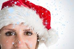Composite image of close up portrait of pretty woman in santa hat smiling Stock Image