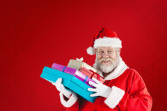 Composite image of close-up portrait of santa claus holding christmas presents Stock Images