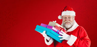 Composite image of close-up portrait of santa claus holding christmas presents Royalty Free Stock Image