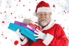 Composite image of close-up portrait of santa claus holding christmas presents Royalty Free Stock Photography