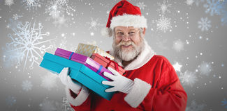Composite image of close-up portrait of santa claus holding christmas presents Royalty Free Stock Photos