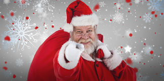 Composite image of close-up portrait of santa claus pointing while carrying christmas bag Royalty Free Stock Photography