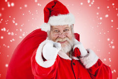 Composite image of close-up portrait of santa claus pointing while carrying christmas bag Stock Photo