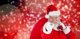 Composite image of close-up portrait of santa claus pointing while carrying christmas bag Stock Image