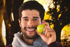 Composite image of close-up portrait of smiling man holding apple. Close-up portrait of smiling man holding apple against fallen leaves on field at park Stock Photography