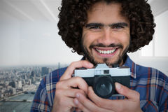 Composite image of close up portrait of smiling photographer holding camera. Close up portrait of smiling photographer holding camera  against city scene in a Royalty Free Stock Images