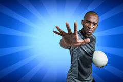Composite image of close-up portrait of sportsman gesturing while standing with rugby ball Stock Photos
