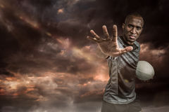 Composite image of close-up portrait of sportsman gesturing while standing with rugby ball Stock Image