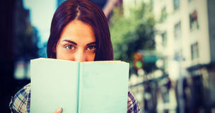 Composite image of close up portrait of woman hiding behind book. Close up portrait of woman hiding behind book against blur view of a modern city Stock Images