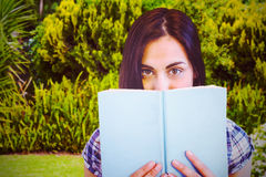 Composite image of close up portrait of woman hiding behind book. Close up portrait of woman hiding behind book against plants and trees growing Royalty Free Stock Images