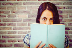 Composite image of close up portrait of woman hiding behind book Royalty Free Stock Photo