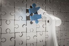 Composite image of close up of robotic arm putting blue jigsaw piece on puzzle 3d Stock Photography