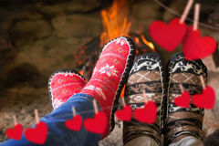 Composite image of close up of romantic legs in socks in front of fireplace. Close up of romantic legs in socks in front of fireplace against hearts hanging on a Stock Photos