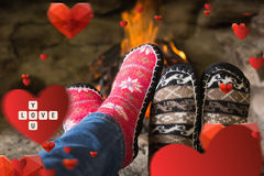 Composite image of close up of romantic legs in socks in front of fireplace. Close up of romantic legs in socks in front of fireplace against love you tiles Stock Image
