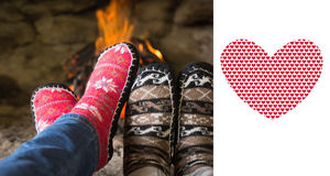 Composite image of close up of romantic legs in socks in front of fireplace. Close up of romantic legs in socks in front of fireplace against valentines day Stock Photo