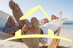 Composite image of close up of sandy feet of couple in a hammock Stock Photography