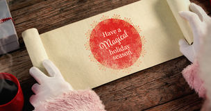 Composite image of close-up of santa claus opening scroll. Close-up of santa claus opening scroll against white and red greetings card Royalty Free Stock Image