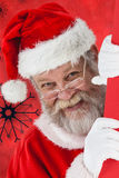 Composite image of close-up santa claus peeking from red board Stock Photo