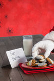 Composite image of close-up of santa claus taking cookies Stock Images