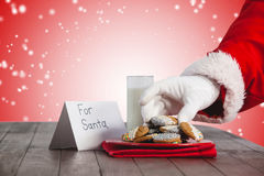 Composite image of close-up of santa claus taking cookies Royalty Free Stock Image