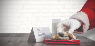 Composite image of close-up of santa claus taking cookies Stock Photography