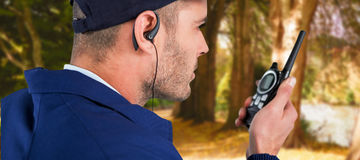 Composite image of close up of security officer talking on walkie talkie. Close up of security officer talking on walkie talkie against row of trees in park stock photo