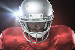 Composite image of close-up of serious american football player in red jersey looking down. Close-up of serious American football player in red jersey looking Royalty Free Stock Photo