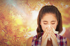 Composite image of close-up of sick woman sneezing in a tissue Stock Photo