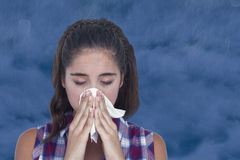 Composite image of close-up of sick woman sneezing in a tissue Stock Image