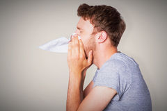 Composite image of close up side view of man blowing nose Stock Images
