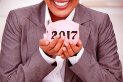 Composite image of close up of a smiling businesswoman holding a piggybank Stock Photos