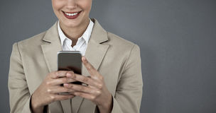 Composite image of close up of smiling businesswoman using mobile phone Royalty Free Stock Photography