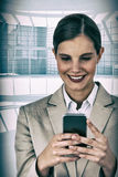 Composite image of close up of smiling businesswoman using mobile phone Royalty Free Stock Images