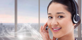 Composite image of close up of a smiling operator posing with a headset Stock Photography