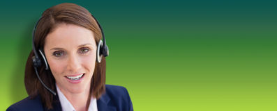 Composite image of close-up of smiling woman talking on microphone headset. Close-up of smiling woman talking on microphone headset against green abstract Royalty Free Stock Photography