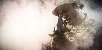 Composite image of close up of soldier aiming with rifle. Close up of soldier aiming with rifle against black royalty free stock photo
